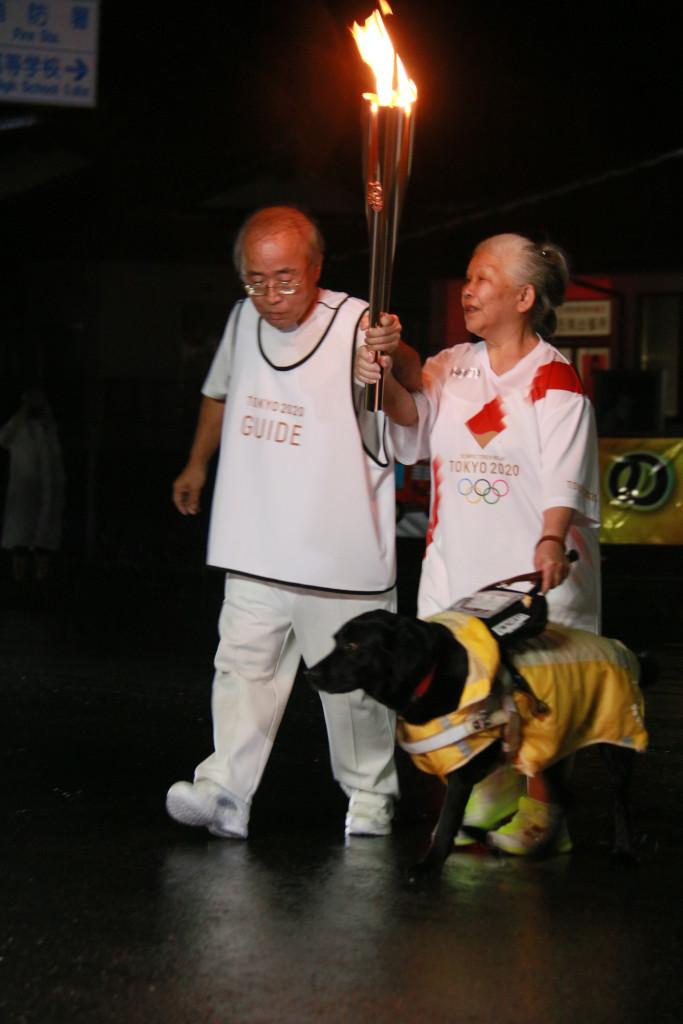 左手に盲導犬ヴォイスをつれ、右手で聖火を高くあげて走る岩谷さんの写真